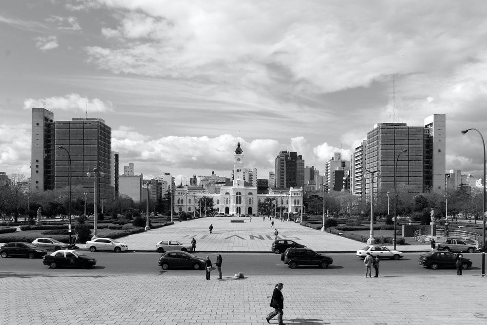 grayscale photo of people walking on street near city buildings during daytime