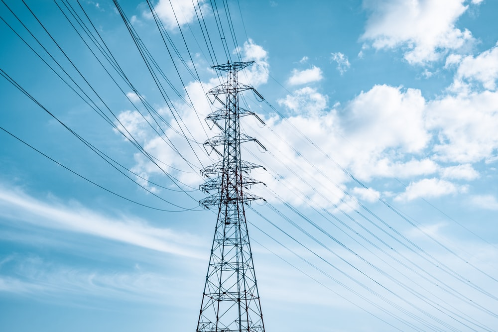 black electric tower under blue sky and white clouds during daytime