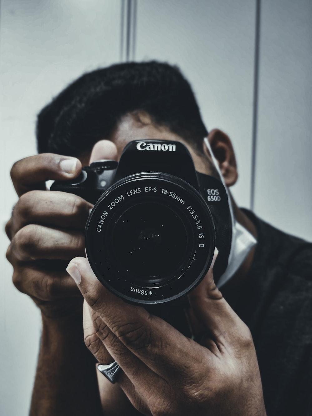 man holding black nikon dslr camera