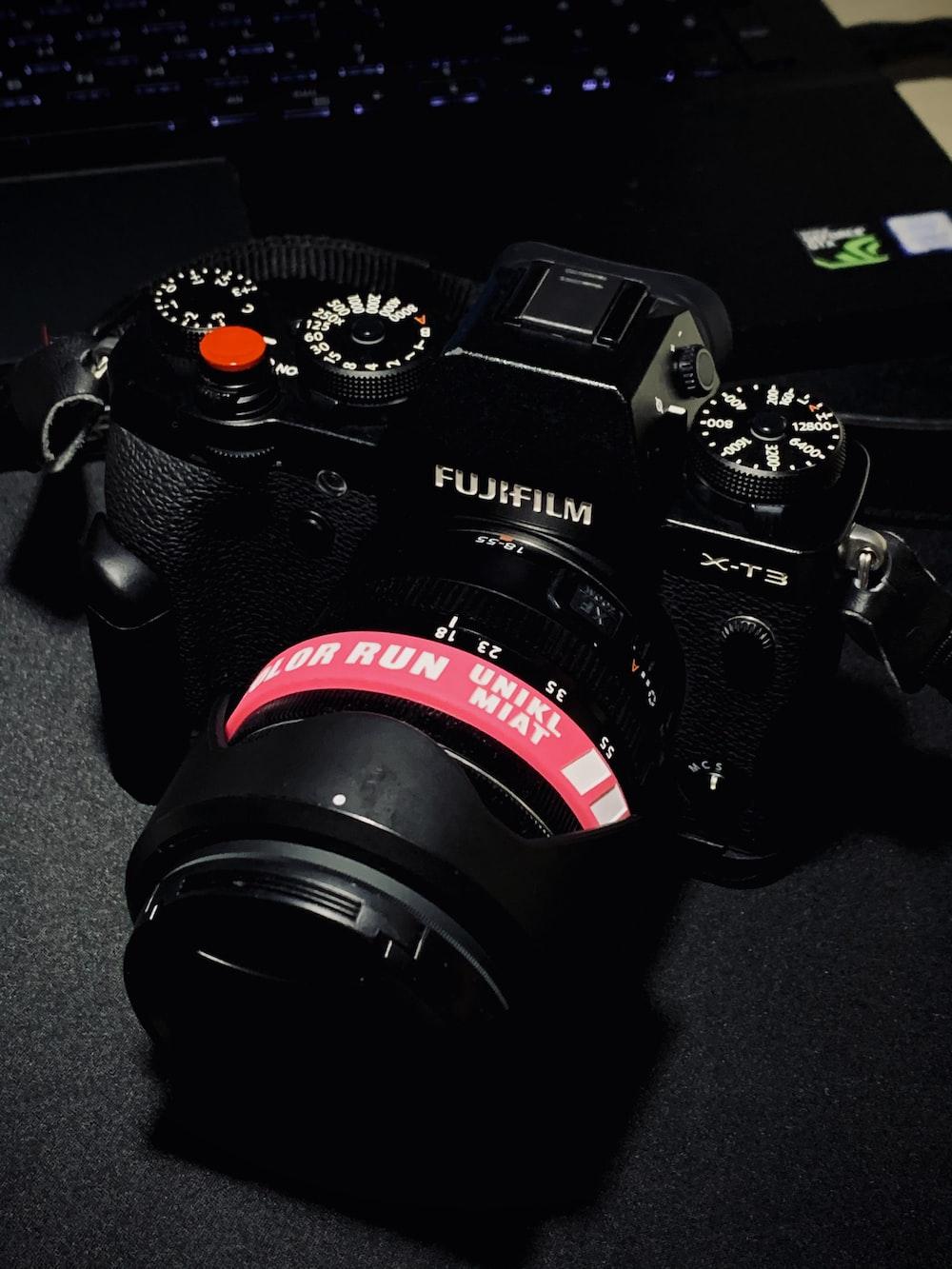 black nikon dslr camera on gray textile