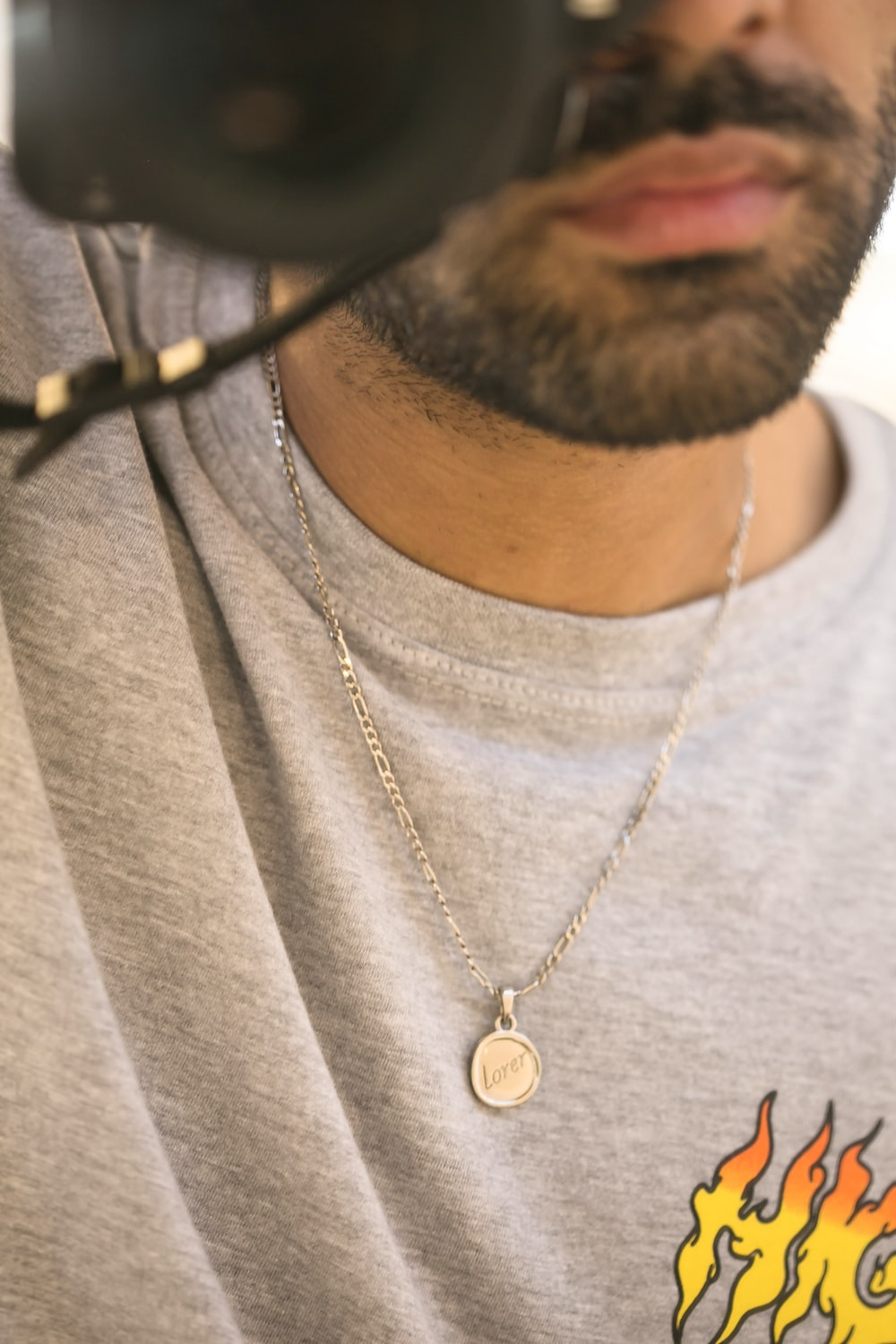 man in gray crew neck shirt wearing silver necklace