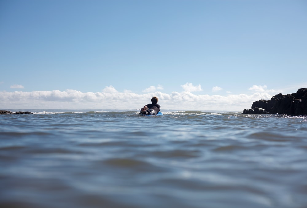 2 person in water under blue sky during daytime