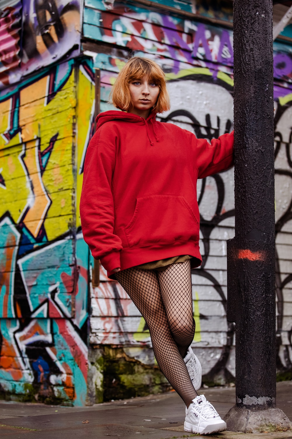 woman in red hoodie and black skirt leaning on black metal fence