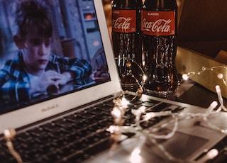 coca cola bottle beside white ipad
