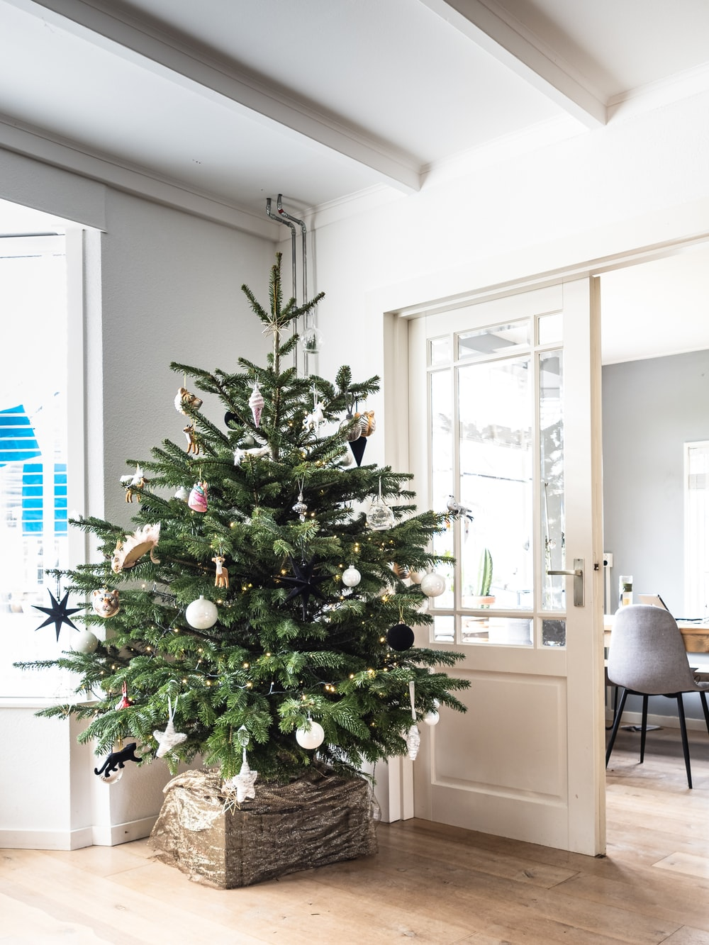 green christmas tree with baubles near white wooden framed glass door