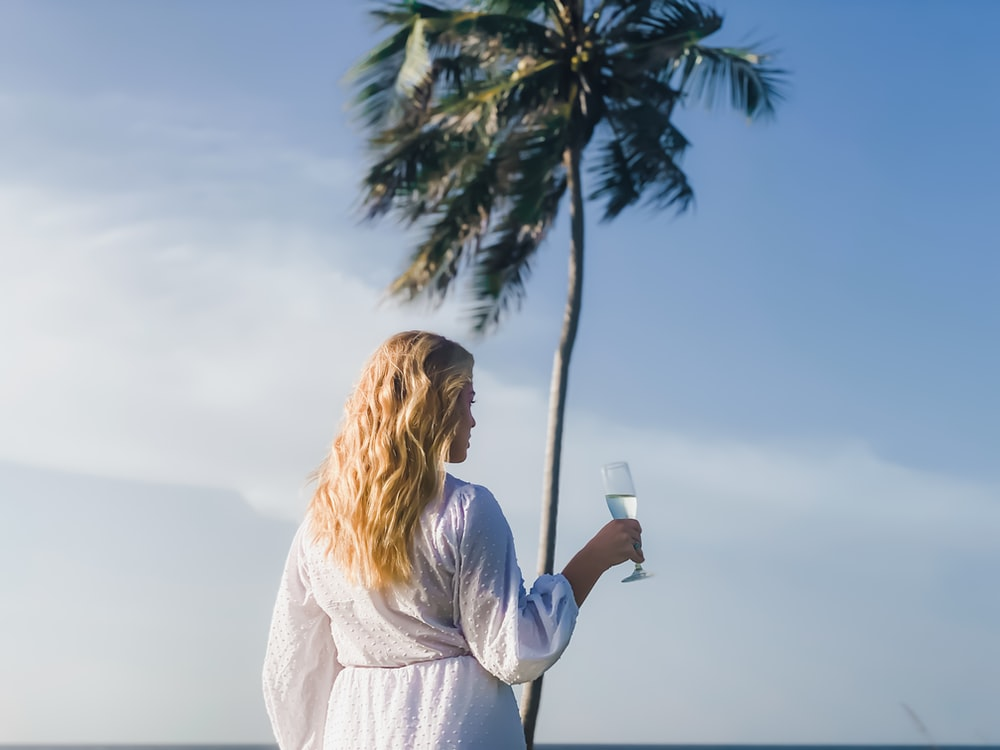 woman in white long sleeve shirt holding white ceramic mug standing beside palm tree during daytime