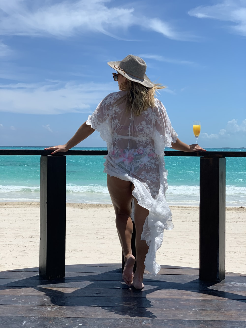 woman in white and pink floral shirt and brown hat standing on beach during daytime