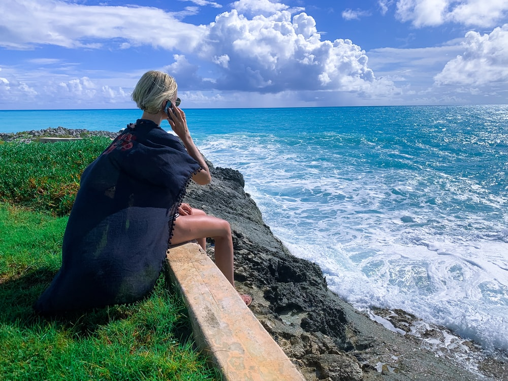 woman in black dress sitting on gray concrete bench near body of water during daytime
