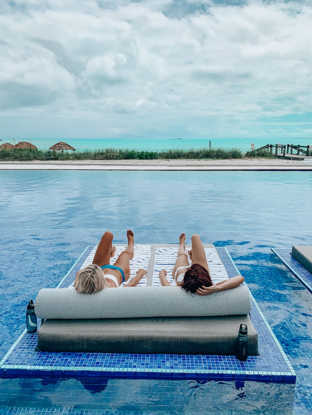 2 women lying on blue towel on blue swimming pool during daytime