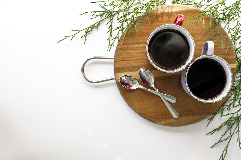 black liquid in white ceramic mug on brown wooden round tray