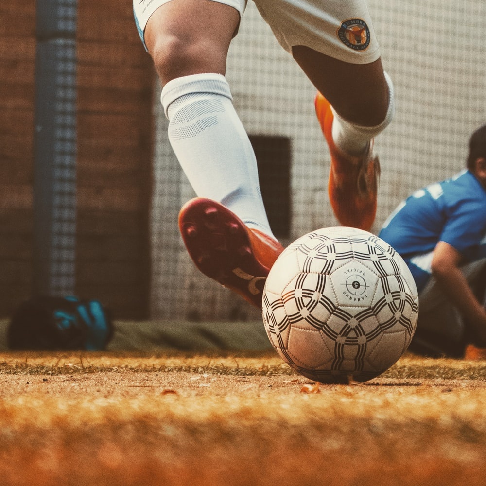 person in white and red soccer jersey kicking soccer ball