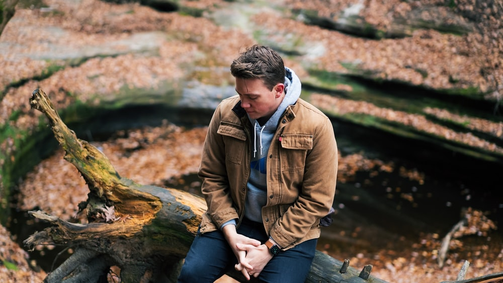 man in brown jacket sitting on brown tree log during daytime