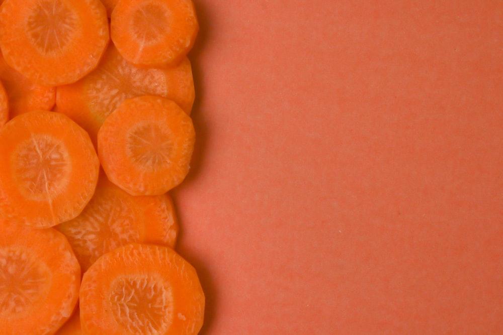 sliced orange fruit on brown surface