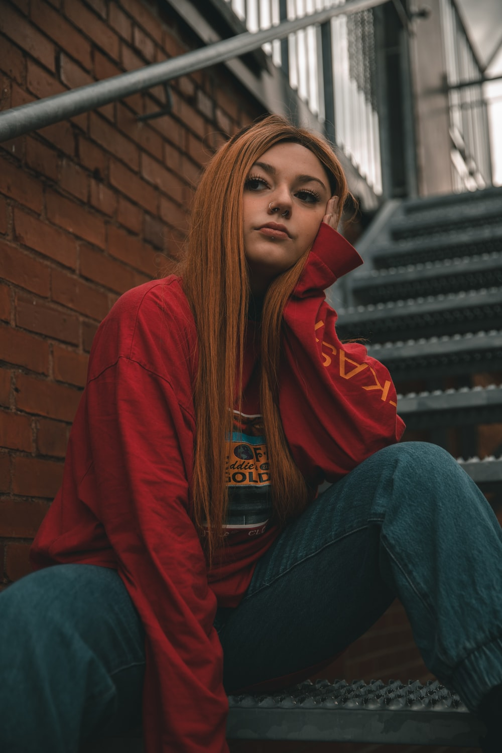 woman in red hoodie and blue denim jeans sitting on stairs