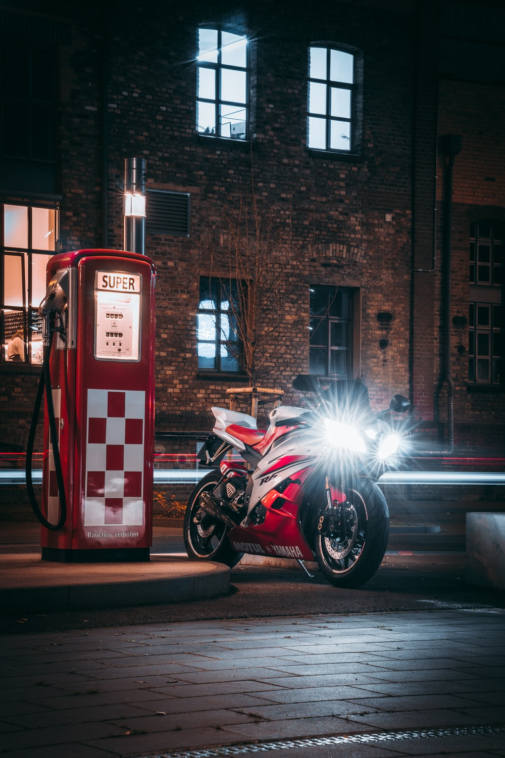 black motorcycle parked beside red and white fire extinguisher