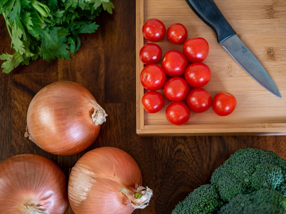 red tomatoes beside green broccoli and green broccoli on brown wooden chopping board