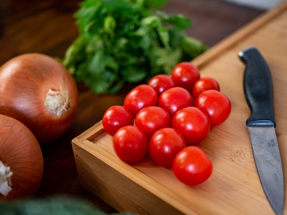 red tomatoes on brown wooden chopping board