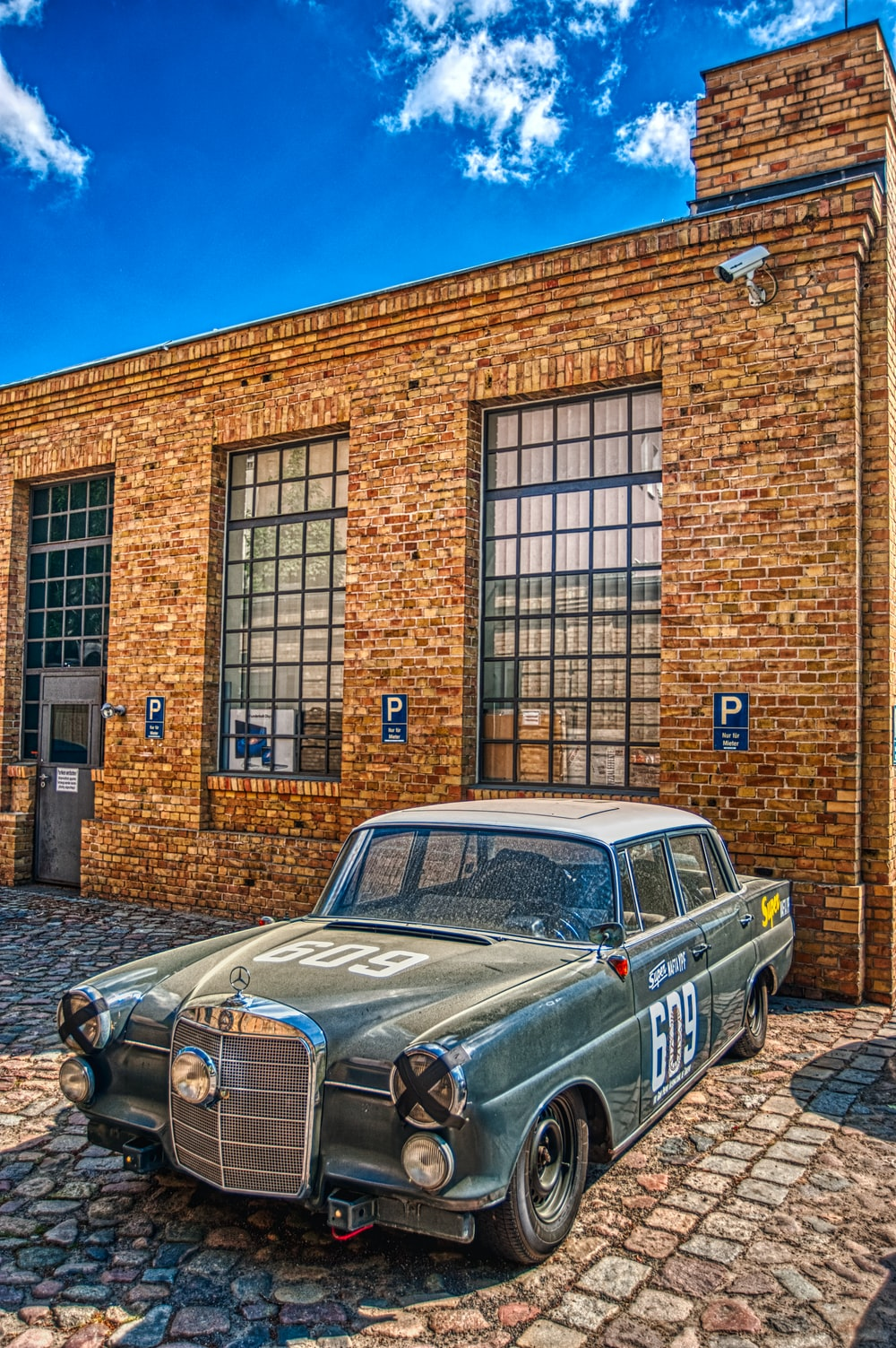 green classic car parked beside brown brick building