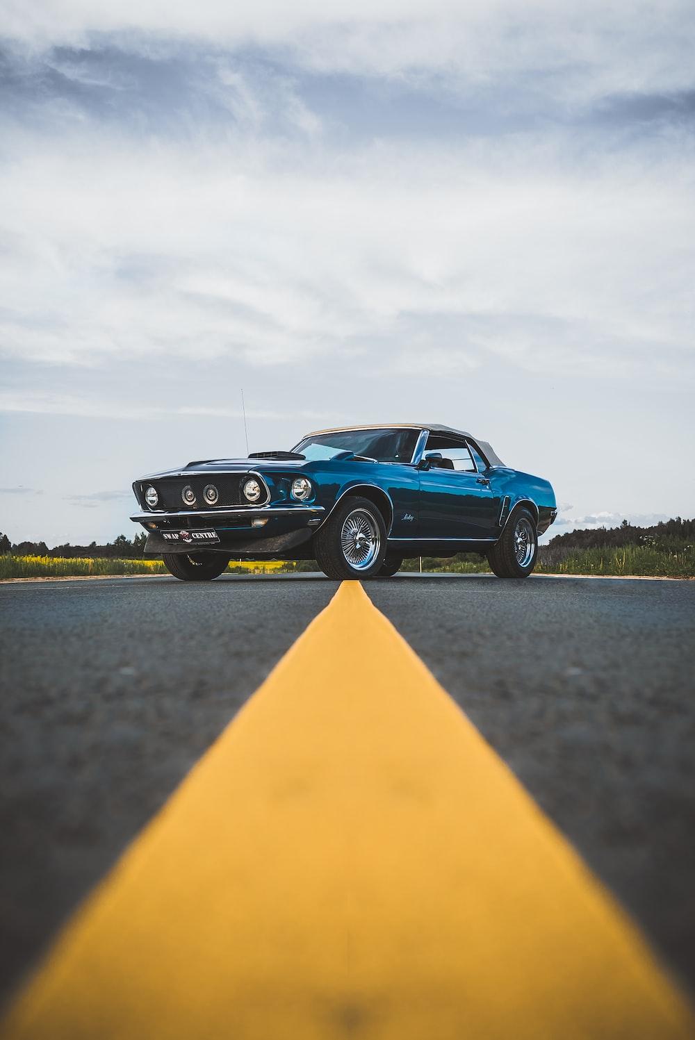 blue chevrolet camaro on road during daytime
