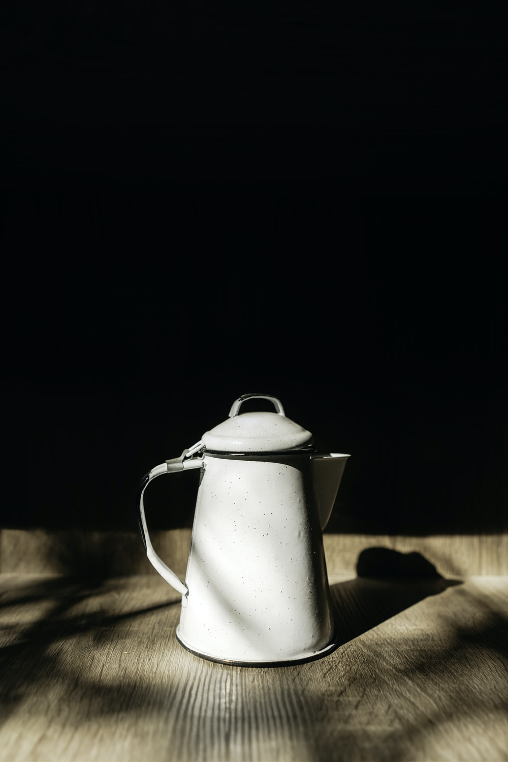 stainless steel pitcher on brown wooden table