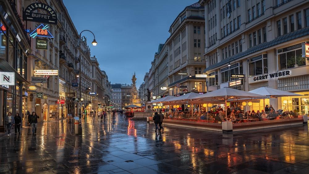 people walking on street between high rise buildings during night time