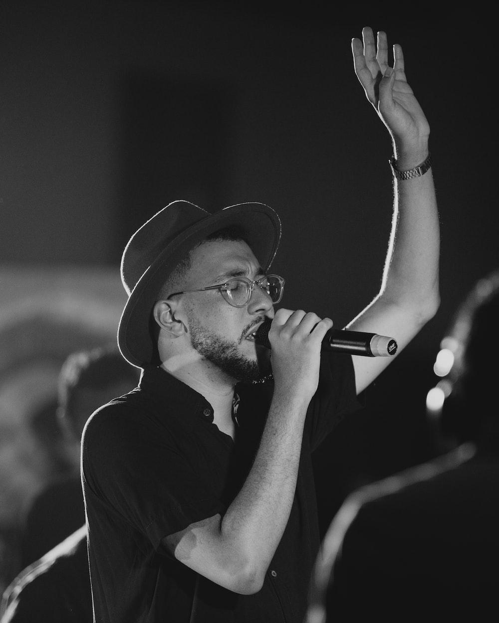 man in black hat holding smartphone
