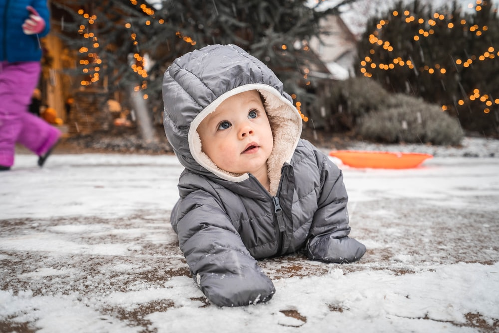child in gray winter jacket lying on snow covered ground