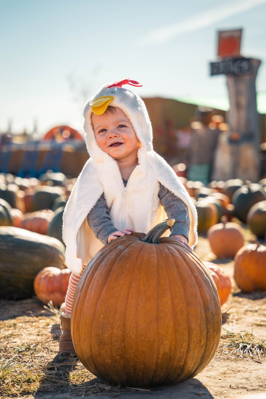 girl in white coat standing on pumpkin during daytime