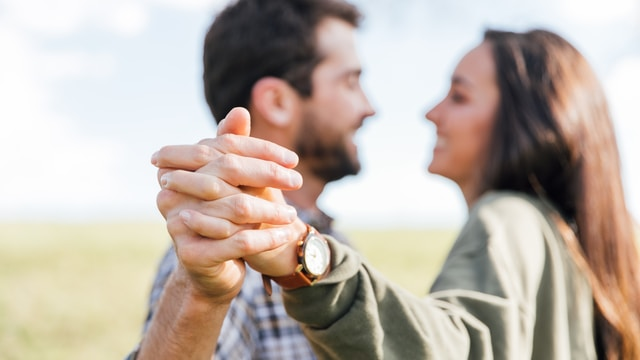 man in gray long sleeve shirt holding womans hand