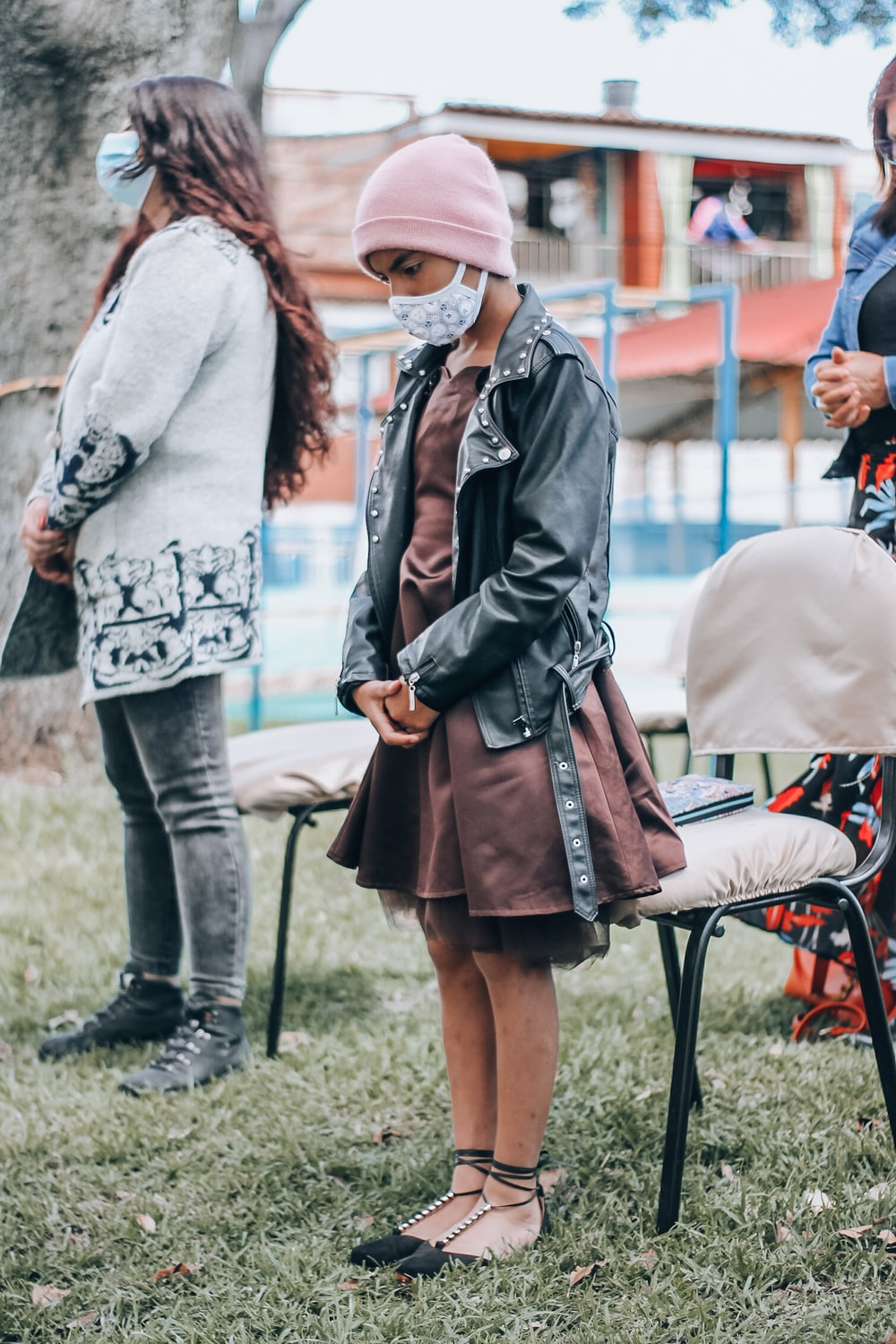 woman in black leather jacket and brown skirt holding brown leather sling bag