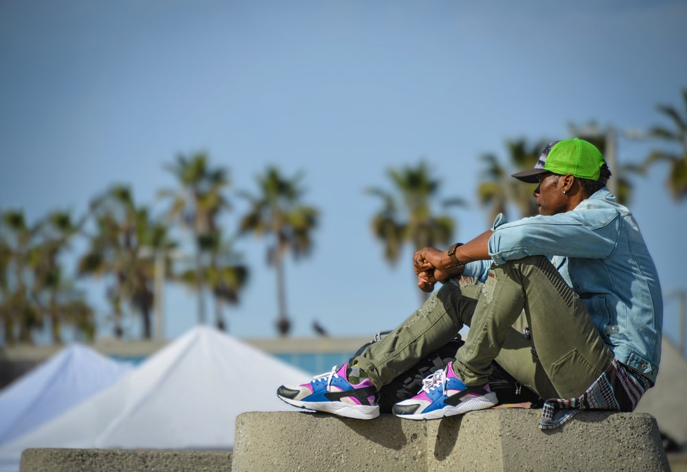 man in green jacket and green cap sitting on white concrete bench during daytime