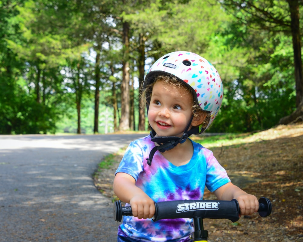 girl in pink and white helmet riding bicycle on road during daytime