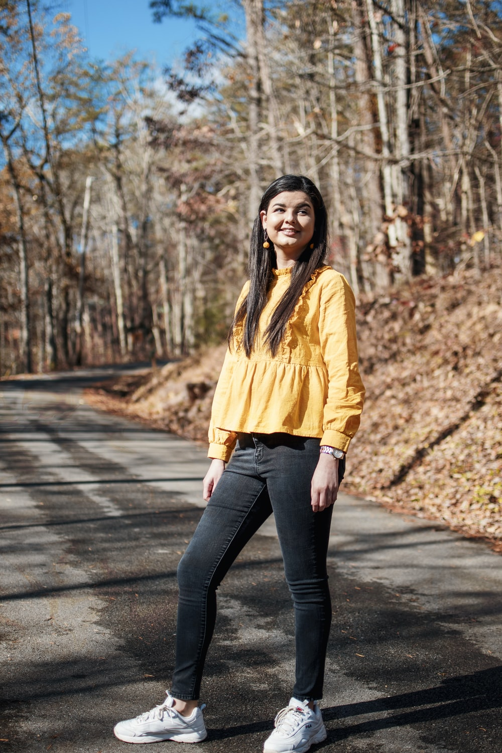 woman in yellow long sleeve shirt and blue denim jeans standing on gray concrete pathway during