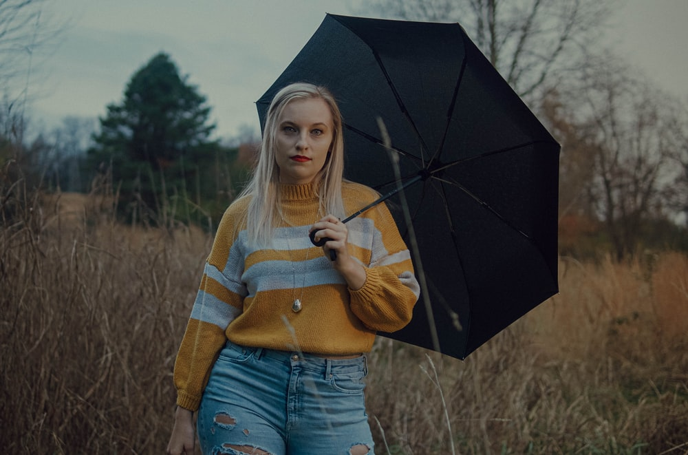 woman in brown and white striped sweater holding umbrella