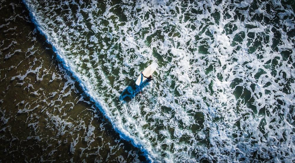 woman in blue bikini lying on white surfboard on beach during daytime