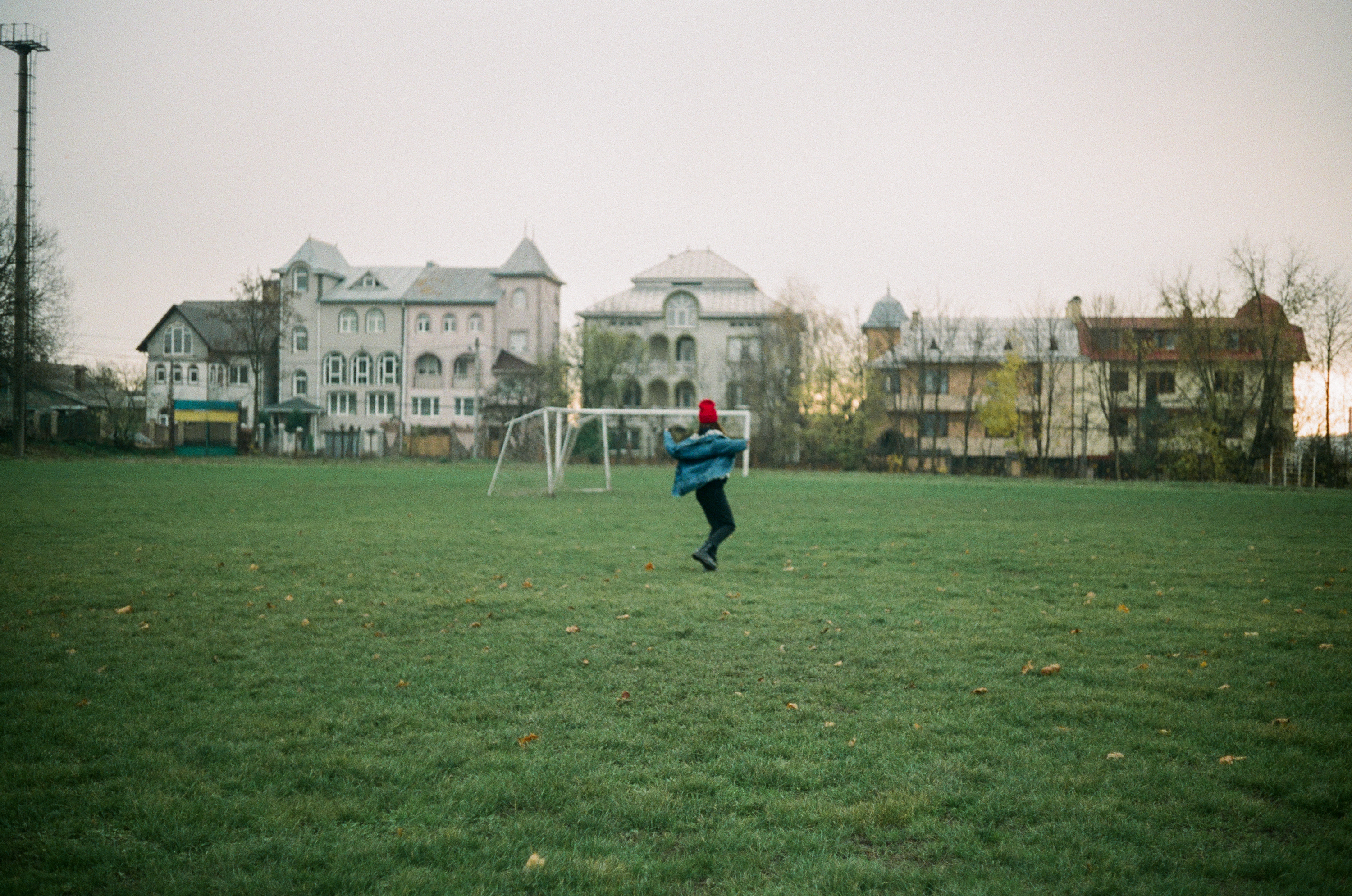 man in blue jacket and black pants walking on green grass field during daytime