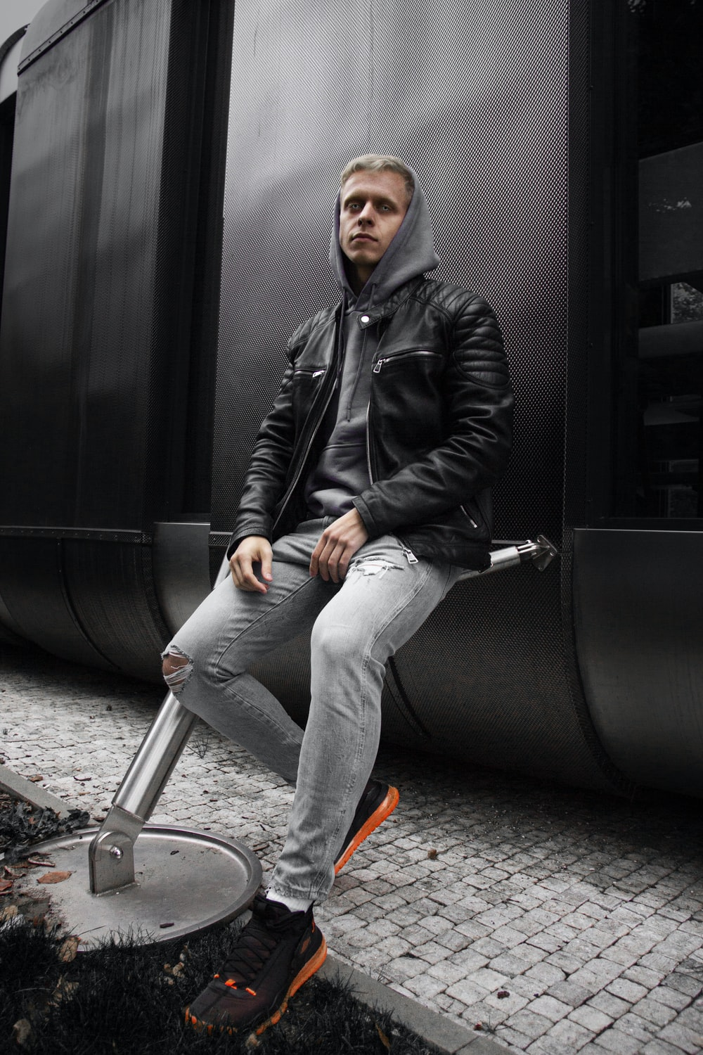 man in black leather jacket and blue denim jeans sitting on gray bicycle