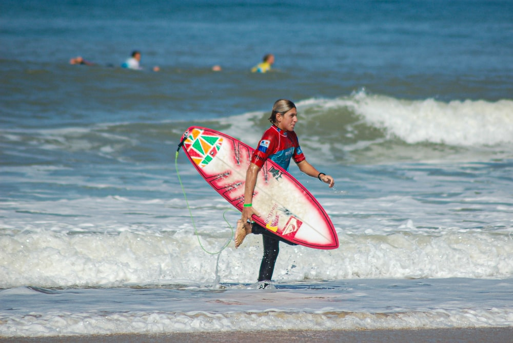 girl in red and black wet suit holding red and white surfboard on beach during daytime