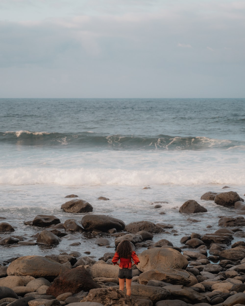 person in red hoodie sitting on rocky shore during daytime