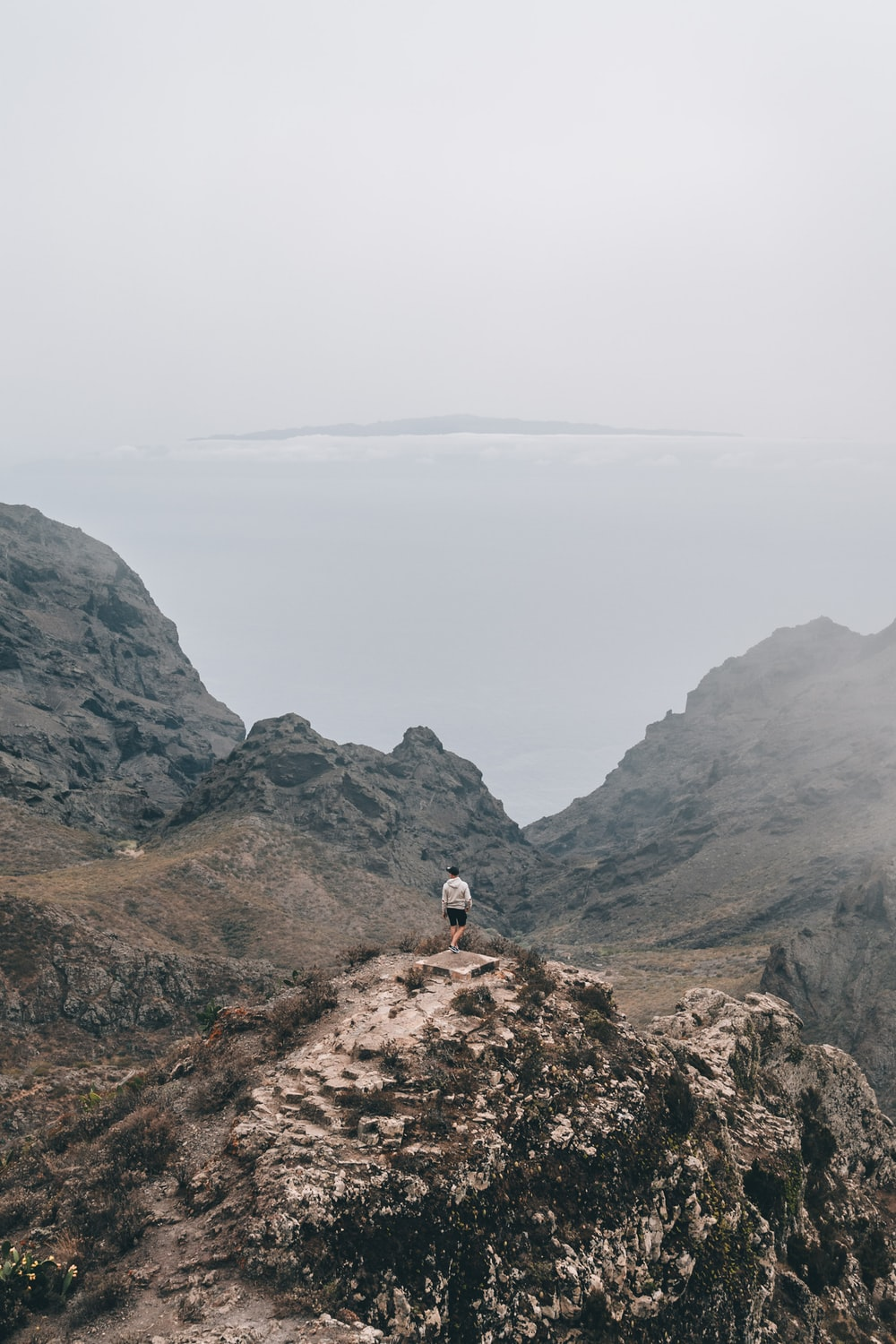 person in white shirt standing on brown rock mountain during daytime