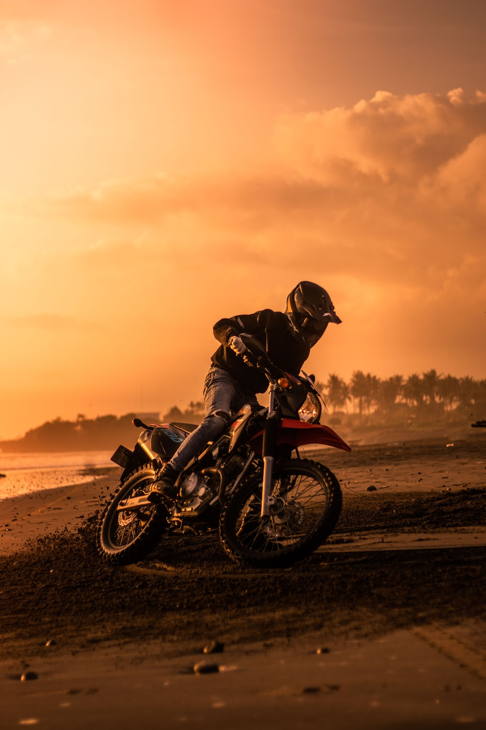 silhouette of man riding motorcycle on beach during sunset