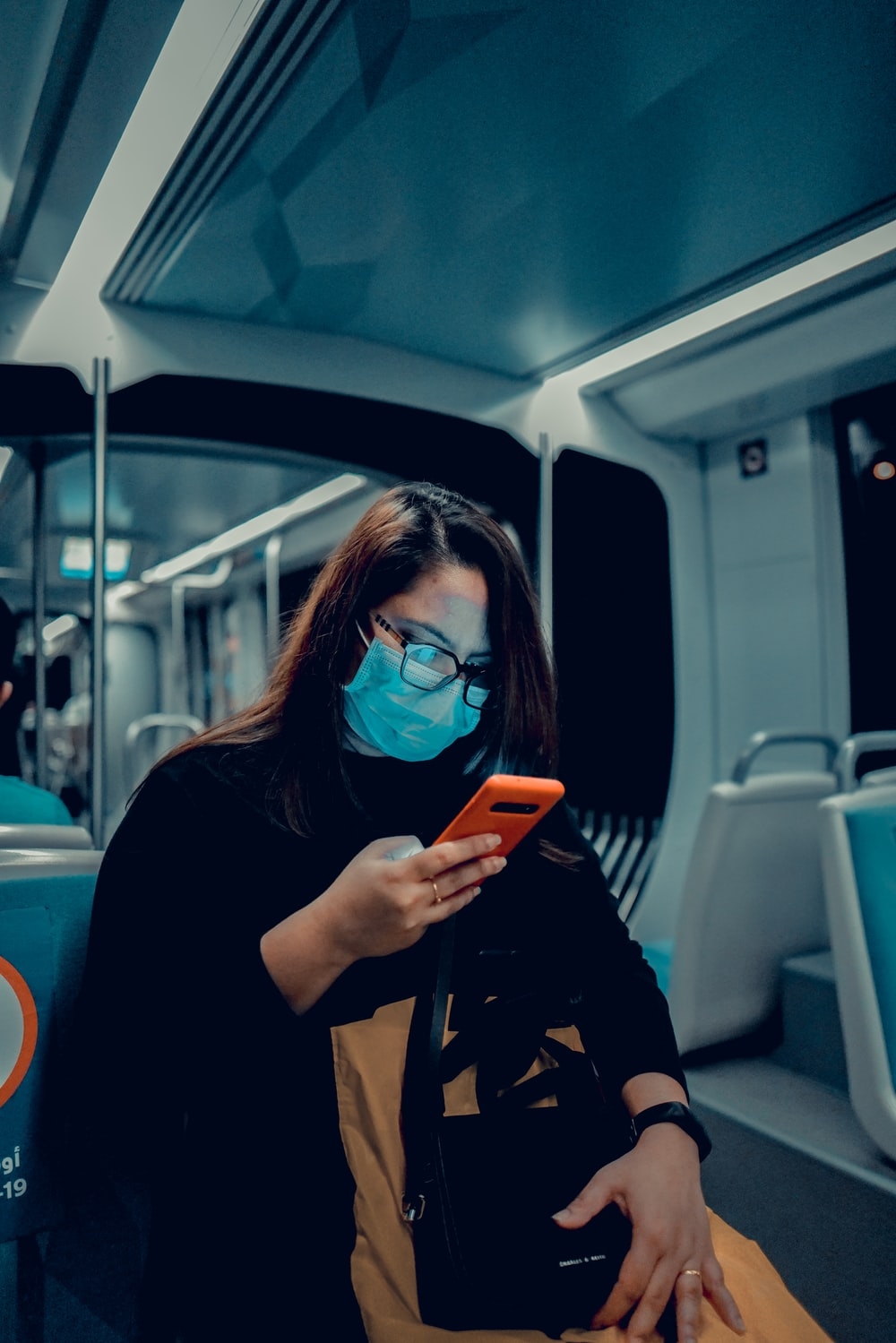 woman in black jacket wearing blue sunglasses holding iphone