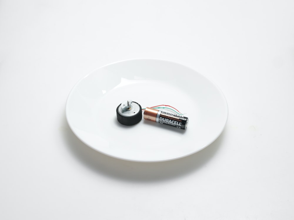 silver and black tube on round white ceramic plate