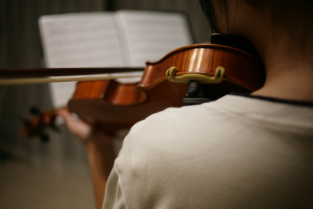 person in white shirt playing violin