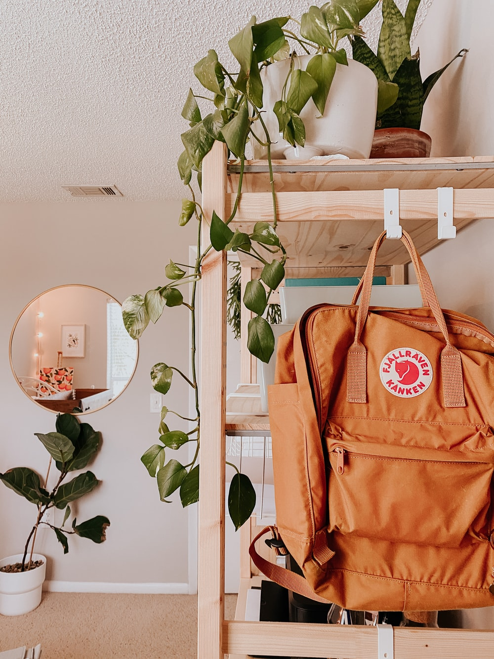 brown leather tote bag hanged on white wooden rack