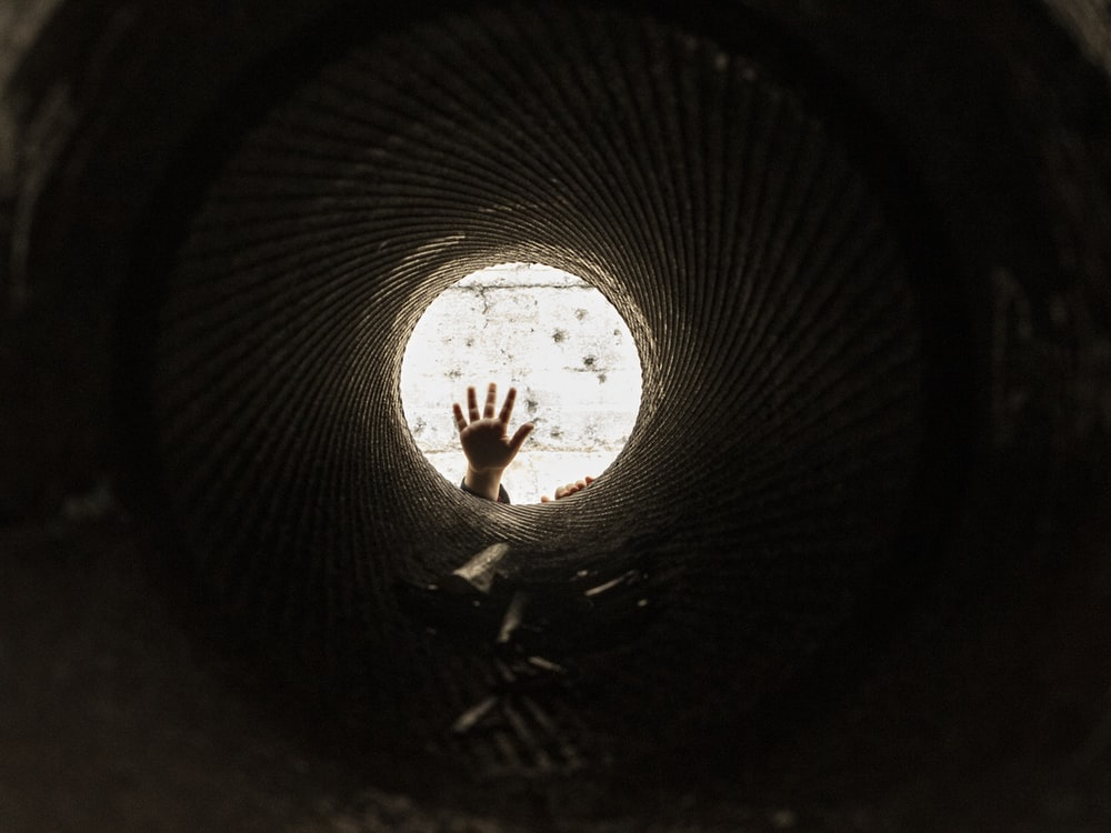 man in black shirt standing on tunnel