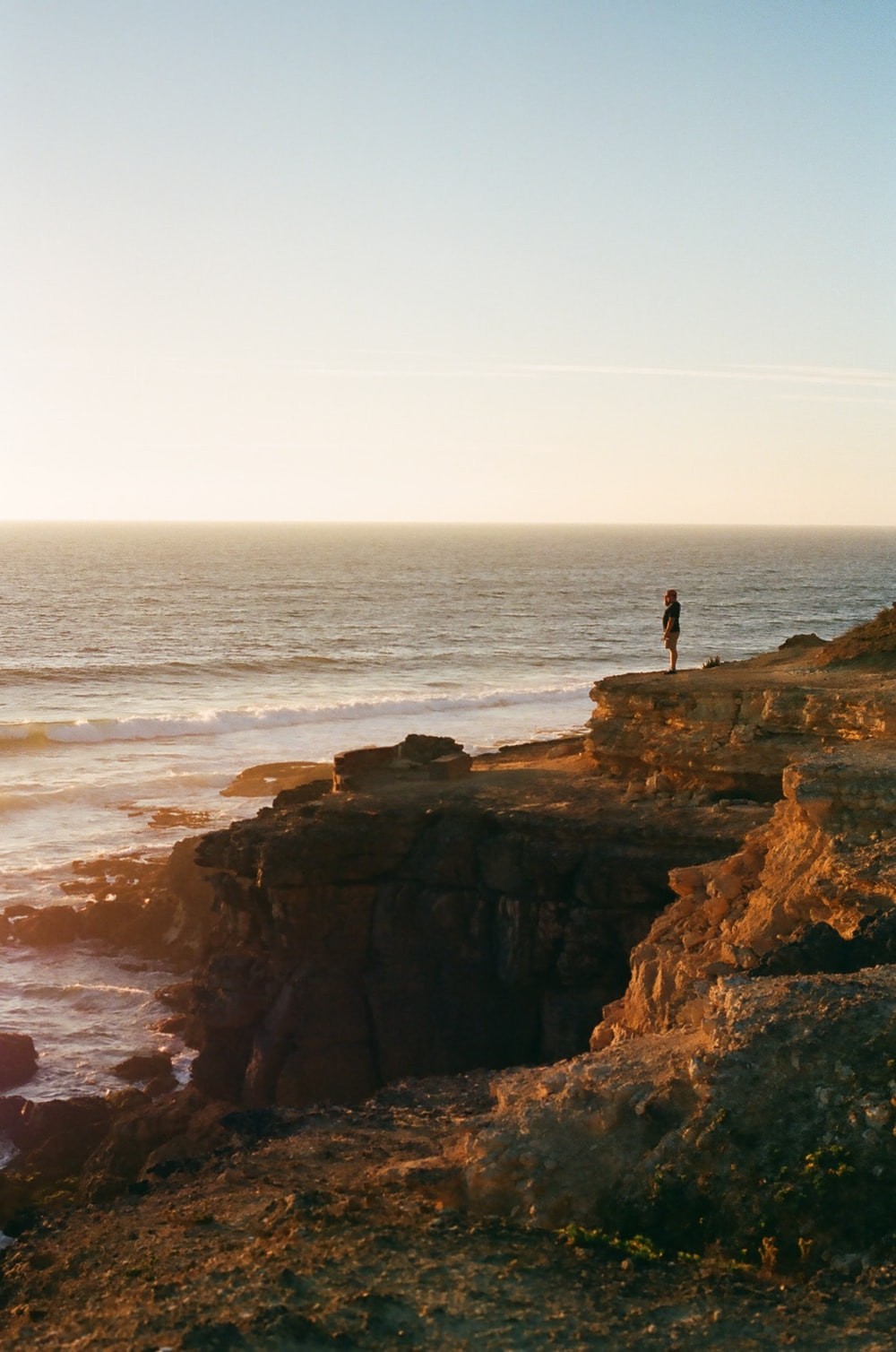 person standing on rock formation near sea during daytime