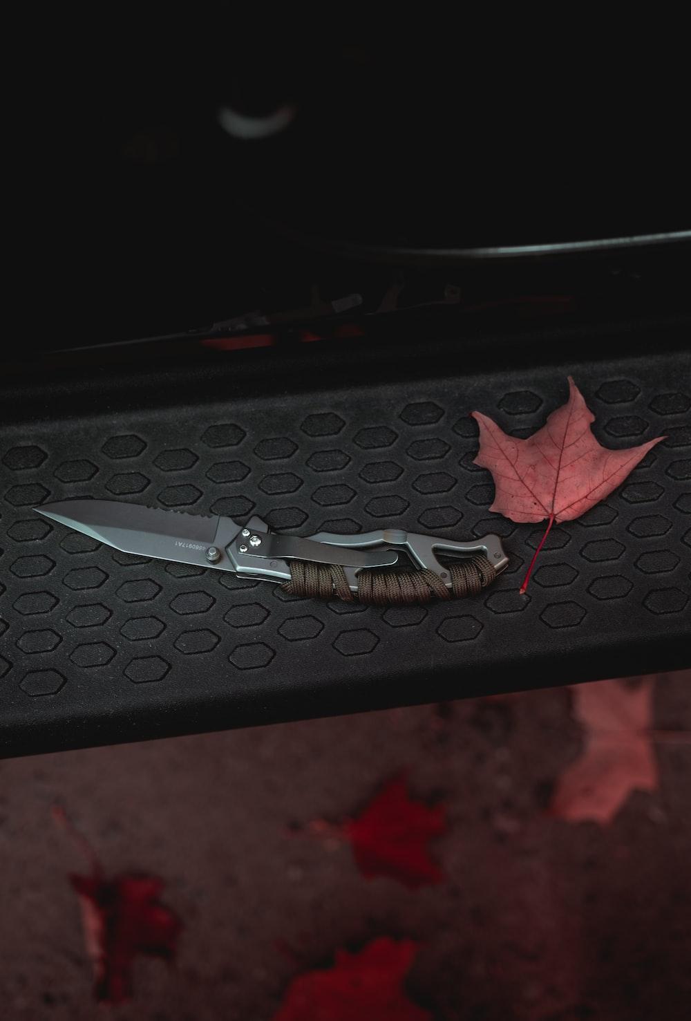 black handled knife on black surface