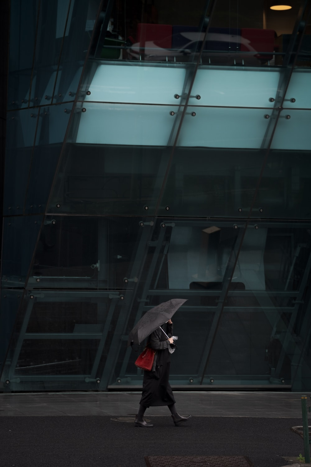 person in black jacket and black pants holding umbrella