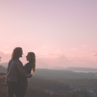 man and woman standing on top of the mountain during daytime